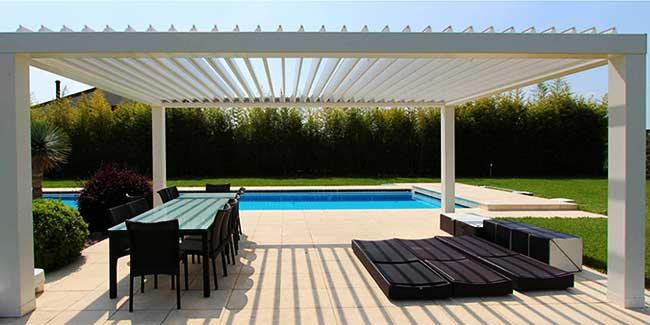 Pergola bioclimatica bianca autoportante montata all'esterno vista piscina