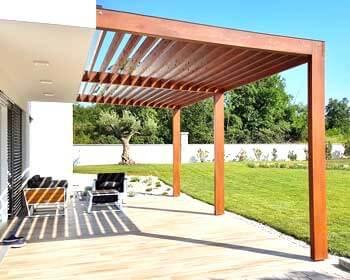 Pergola moderna in legno addossata alla casa che si affaccia sul giardino